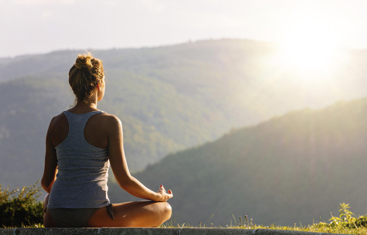 Young woman meditating on the high mountain and looking into sun