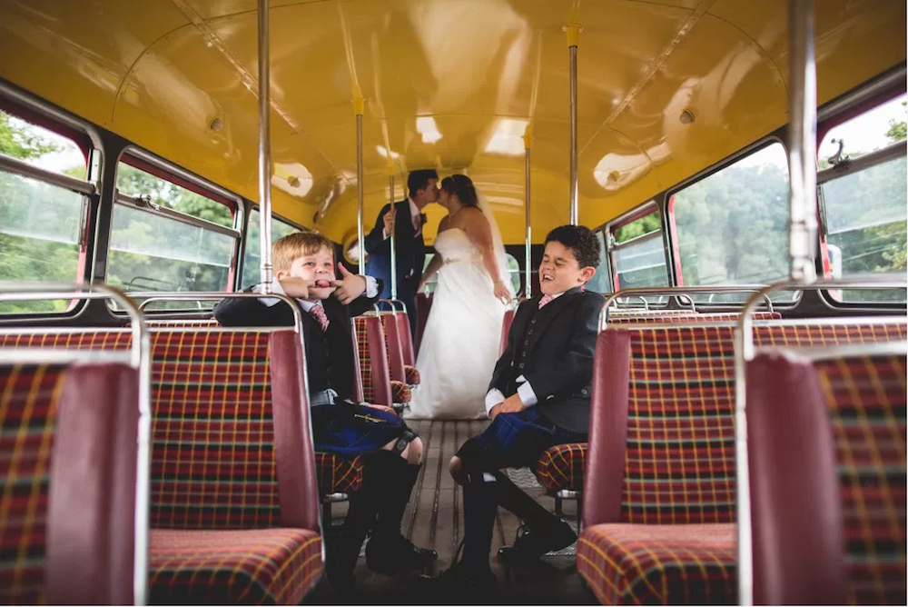 Two page boys on a bus with a wedding couple