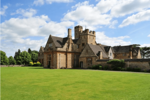 attractive old stone school building with green lawns to the front